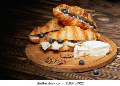 Croissants with Camembert cheese and blueberries on a dark background. Place for text, copy paste.