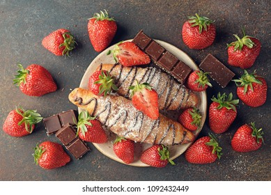 Croissants with chocolate and strawberries on a brown background