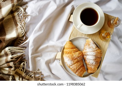 Croissants and coffee for breakfast in bed. Concept of cozy holiday