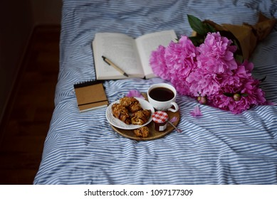 Croissants, coffee  cup and bouquet of peonies on the bed