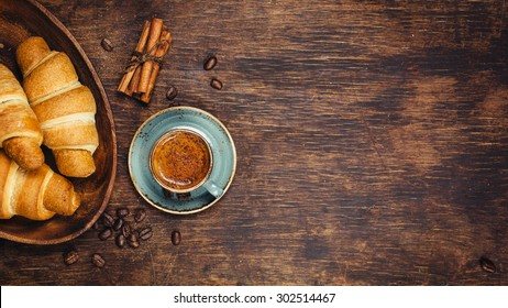 Croissants and coffee on a rustic dark background. Food background with copyspace