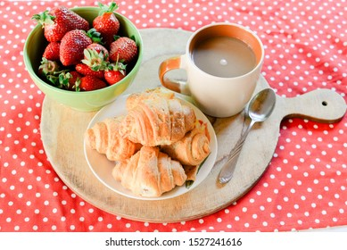 croissants and coffee, a plate of strawberries on the table