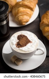 Croissants with cup of coffee on wooden background