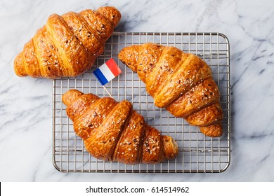 Croissants with French flag on cooling rack. Marble background. Top view.