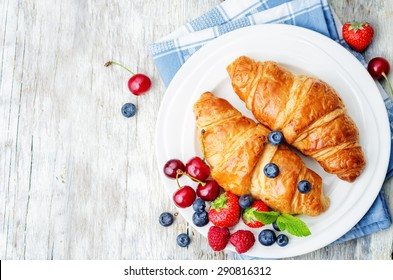 croissants with fresh berries on a white wood background.the toning. selective focus