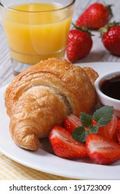 Croissants with fresh strawberries and orange juice close up. vertical