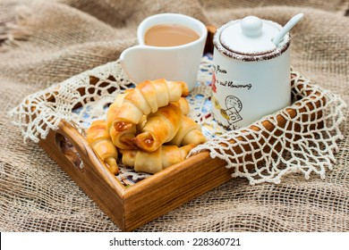 croissants with jam and coffee on a tray