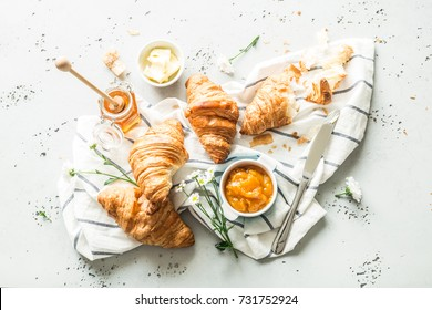 Croissants, jam, honey, butter and flowers. Continental breakfast ingredients captured from above (top view, flat lay). Napkin and grey stone worktop as background.