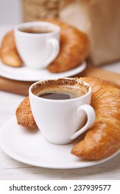 Croissants next to two cups of coffee