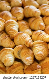 Croissants on bakery shelf.