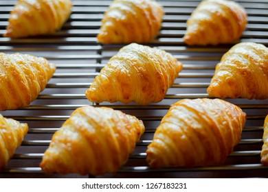 Croissants on bakery shelf.