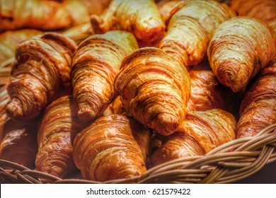 Croissants on a basket weave in a bakery shop.
