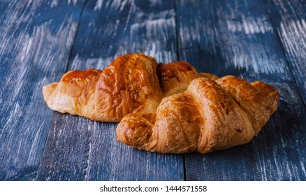croissants on a blue wooden background, delicious pastries with a ruddy crisp close up