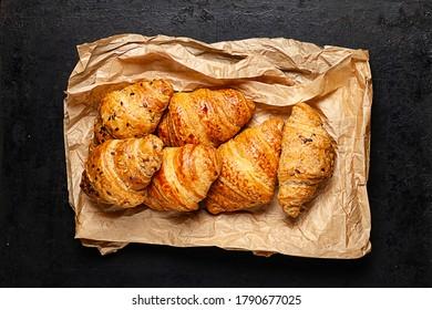 croissants sobre papel de cocción cruzado sobre fondo rústico antiguo