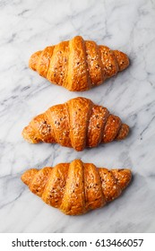 Croissants on marble table. French traditional pastry. Top view.