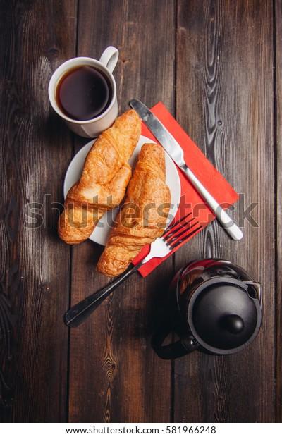 croissants on a plate, coffee kurzhke knife on a red napkin.