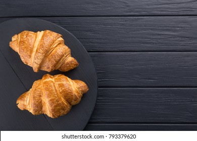 Croissants on a wooden board and a black wooden table. Free space for text. View from above. Top view.