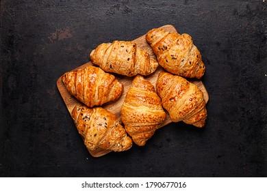 croissants sobre un tablero de madera sobre un fondo rústico antiguo