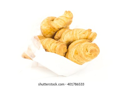 Croissants in plastic bags on white background.