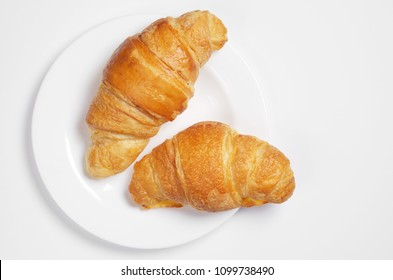 Croissants in plate on white background, top view