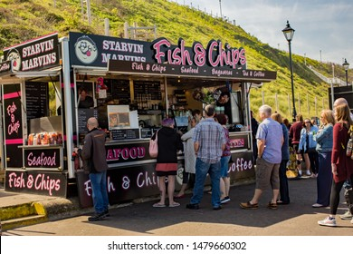 Cromer, Norfolk, UK – April 19 2019. People forming an orderly queue at Starvin Marvin's mobile fish and chip van on Cromer sea front.