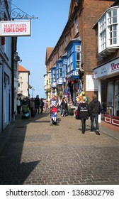 Cromer, Norfolk/UK - April 30th 2011: Cromer High Street with man pushing child in pushchair and fish and chip shop.