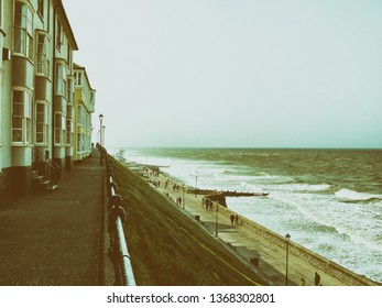 Cromer, Norfolk/UK - April 30th 2011: Cromer seafront with people strolling along the promenade and waves. Classic green and brown colour photo.