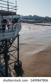Cromer, UK - April 20, 2019: People catching crabs with buckets lowered from Cromer pier. Cromer is a seaside town in Norfolk and a popular family holiday destination in UK.