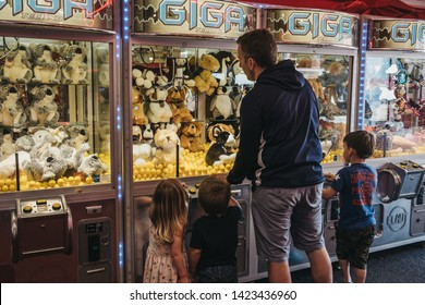 Cromer, UK - April 20, 2019: Father and kids trying to win a soft toy from machine at the arcade by the seaside in Cromer, a seaside town in Norfolk and a popular family holiday destination in UK.