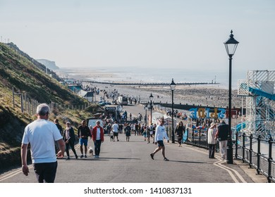 Cromer, UK-April 20, 2019: People walking on a coastal path alongside the beach in Cromer, a seaside town in Norfolk and a popular holiday destination in UK.