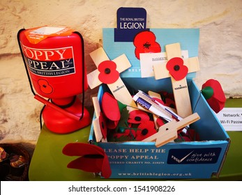 CROMFORD, UNITED KINGDOM, 26th October, 2019: A poppy appeal donation box with crosses and poppies to buy to honour the war dead and pay respect through remembrance