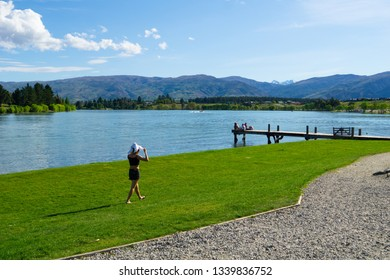 CROMWELL NEW ZEALAND - OCTOBER 21; Lake Dunstan scene young woman walks along lake edge and group young people sit together on end of jetty Cromwell New Zealand October 21 2018 Cromwell New Zealand