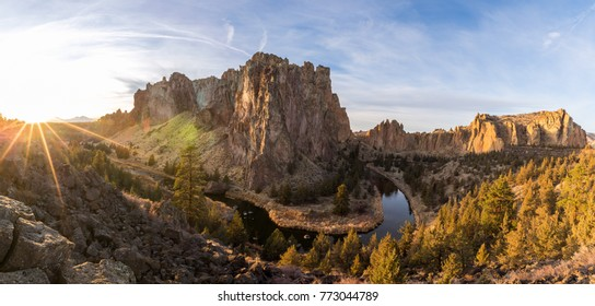 The Crooked River winds around Smith Rock State Park in a panorama during sunset in Central Oregon.