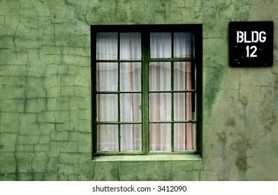 Crooked window in green wall