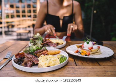 Crop anonymous female wearing stylish outfit eating delicious breakfast including scrambled eggs and grilled bacon served on wooden table with sweet freshly baked pancakes in sunny outdoor cafe