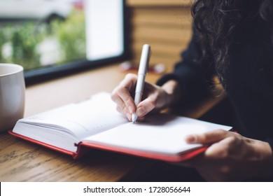 Anonyme weibliche Schreibstifte mit Stift im Notizbuch kreuzen, während sie durch das Fenster sitzen und eine Tasse heißen Drinks in sanftem Licht haben