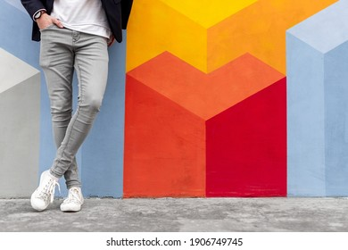 Crop anonymous male in trendy gray skinny jeans and white sneakers holding hand in pocket while leaning against colorful wall