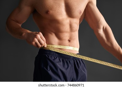Crop anonymous man with muscular torso measuring waist with tape.