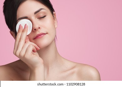 Crop attractive young female cleansing face with a cotton pad on a pink background in studio