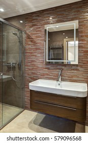 Crop of bathroom in modern style with element of ceramic and stones on wall. Square mirror and sink with wooden cupboard under. Glasses shower near.