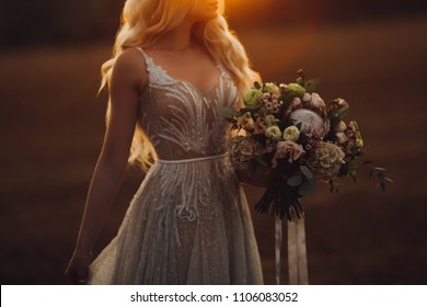 Crop of beautiful long haired blondie bride wearing elegant ivory lace wedding dress, holding by hands and looking at big colorful wedding boquet. Walking in field at sunset time.
