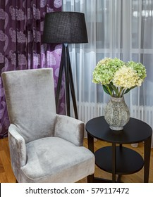 Crop of bedroom with gray velor armchair near rounded wooden table. Green and white hydrangea in vase on table. High black lamp and violet curtains in print.