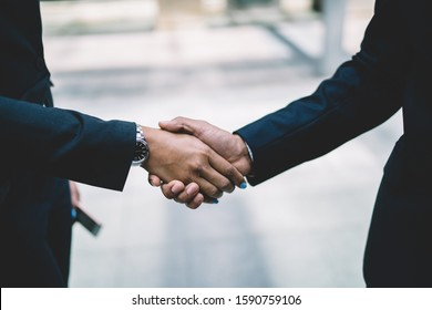 Crop business coworkers in strict formal black suits with watch on wrist shaking hands in street in downtown.Partnership meeting concept. Successful deal agreement handshake. Greeting and support