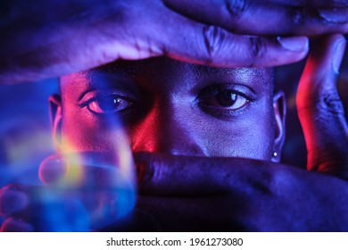 Crop calm African American male glancing through camera hand gesture while standing in dark studio in blurred lights