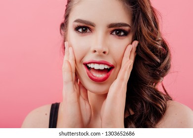 Crop cheerful attractive woman with hands on cheeks looking at camera on pink background