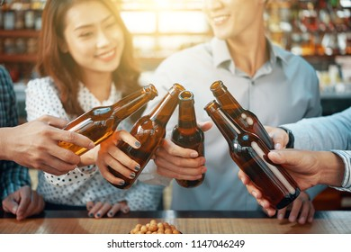 Crop cheerful friends clinking with beer bottles in bright sunlight standing at counter in bar