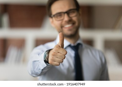 Crop close up blurred background of smiling Caucasian man show thumb up give recommendation. Happy male client or customer recommend good quality service or company. Acknowledgment concept.