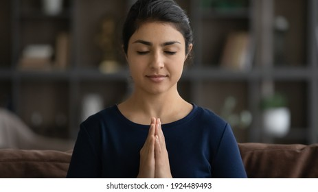 Crop close up of calm Indian woman with eyes closed hold hands in prayer meditate at home. Young mixed race female believer pray to God, feel superstitious religious. Faith, religion concept.