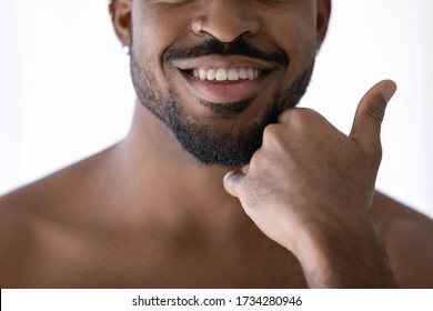 Crop close up of happy african American young man touch beard stubble after shaving in bathroom, smiling biracial male satisfied with shaved bristle after shower in bath, body hygiene concept