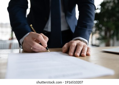 Crop close up of male CEO or boss in suit stand in office put signature on paper document making agreement. Businessman sign paperwork close business financial deal at workplace. Legislation concept.